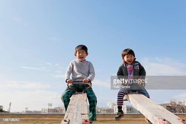 two boys playing on the seesaw with a smile. - seesaw stock pictures, royalty-free photos & images