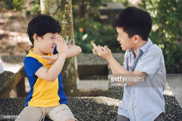 two boys playing outdoors - ultraman stock pictures, royalty-free photos & images