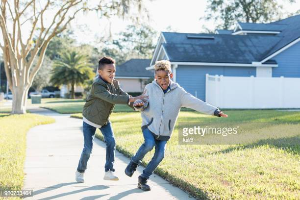 two boys playing outdoors, sibling rivalry - mixed wrestling stock pictures, royalty-free photos & images