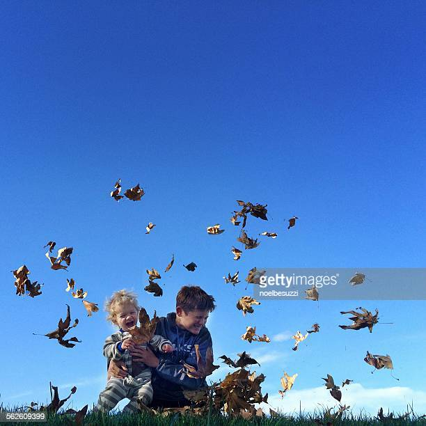 two boys playing outdoors with autumn leaves - taken on mobile device stock photos and pictures