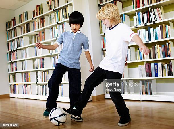 two boys playing soccer in library