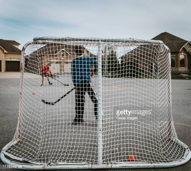 two boys playing street hockey outside with net in the foreground. - アイスホッケーグローブ ストックフォトと画像