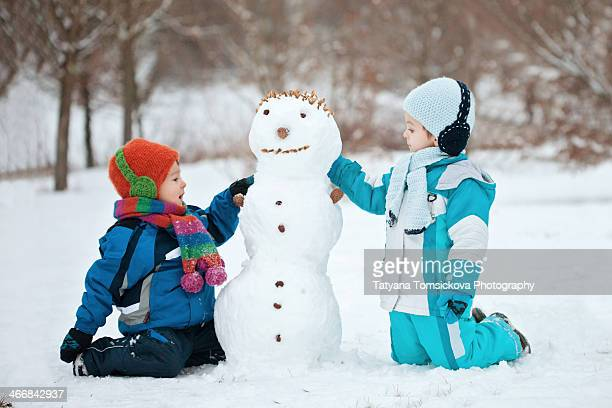 Two boys, playing with a  snowman