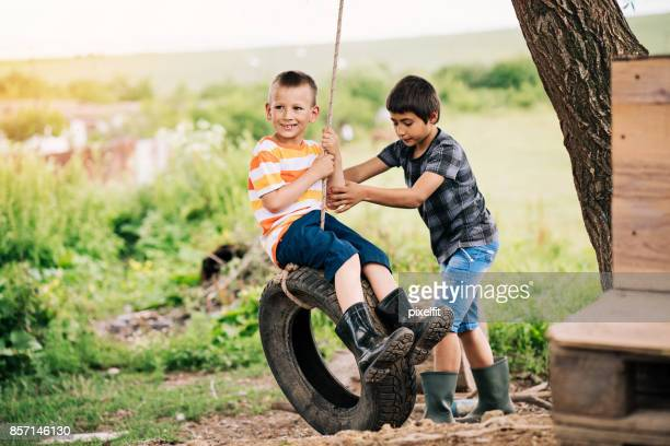 Two boys playing with a tire swing