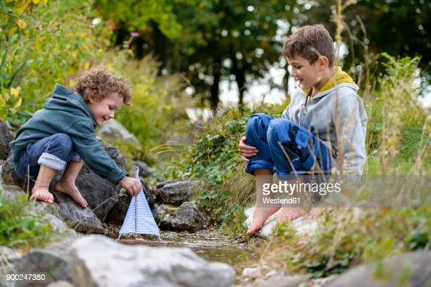 two boys playing with a toy boat in a brook - nur kinder stock-fotos und bilder