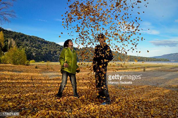 two boys playing with autumn leaves - radicella stock-fotos und bilder