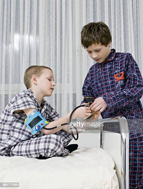 two boys playing with blood pressure meter - newhealth stock pictures, royalty-free photos & images