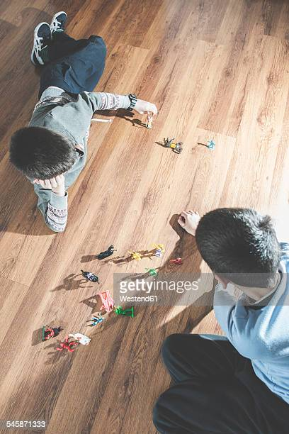 Two boys playing with miniature figurines on the floor at home