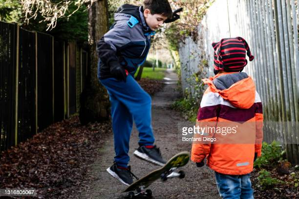 uk, two boys playing with skateboard - jacket stock pictures, royalty-free photos & images