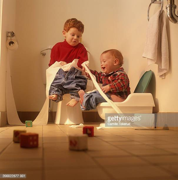 Two boys (9 months to 2 years) playing with toilet paper in bathroom