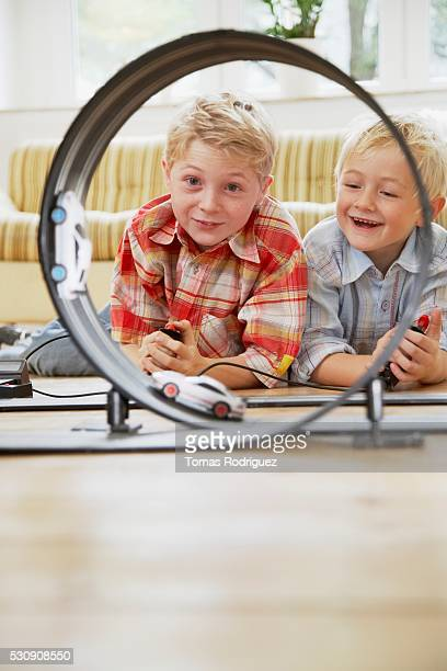 Two boys playing with toy cars