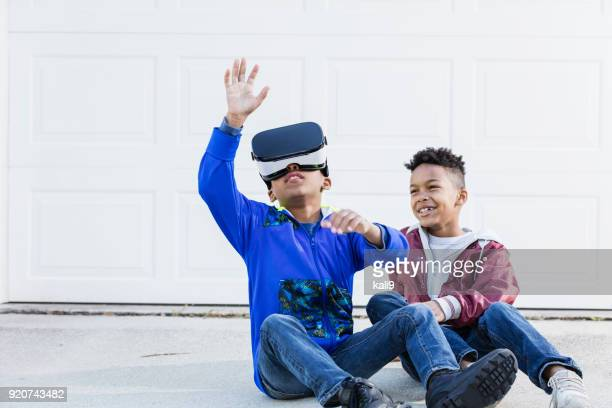 Two boys playing with virtual reality headset