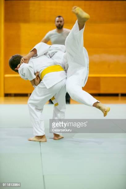 deux garçons pratiquant le judo avec leur instructeur - judo photos et images de collection