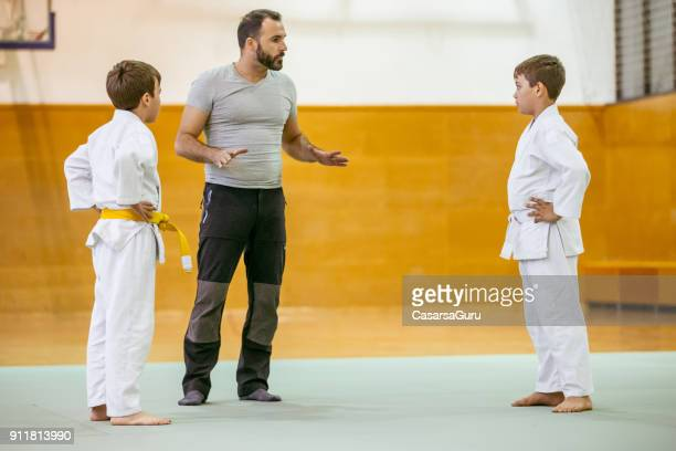 two boys practicing judo with their instructor - submission combat sport stock pictures, royalty-free photos & images