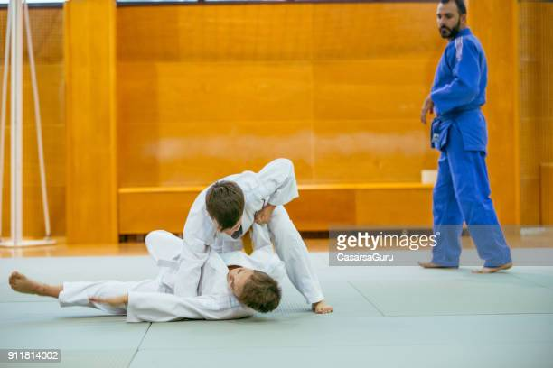 two boys practicing judo with their instructor - judo stock photos and pictures