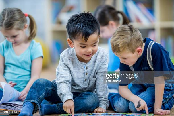 two boys reading a book - 6 7 years photos stock photos and pictures