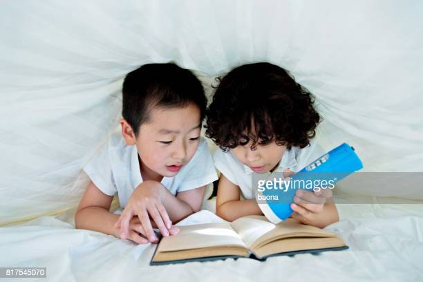 Deux garçons, lire un livre sous les couvertures