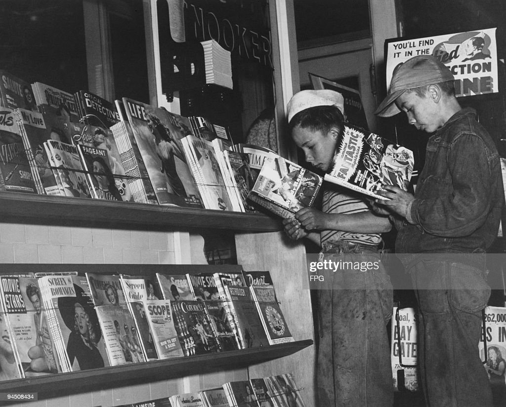 Two boys reading reading comics at a news stand, USA, circa 1955.