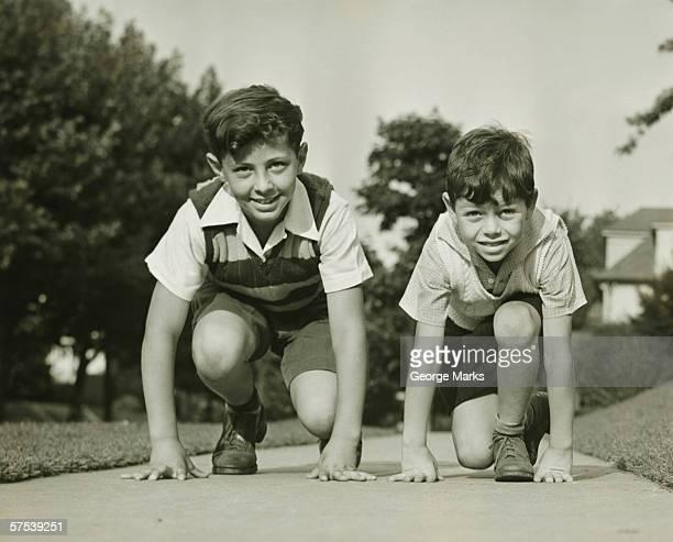 Two boys (8-9) (12-13) ready to start running, (B&W)