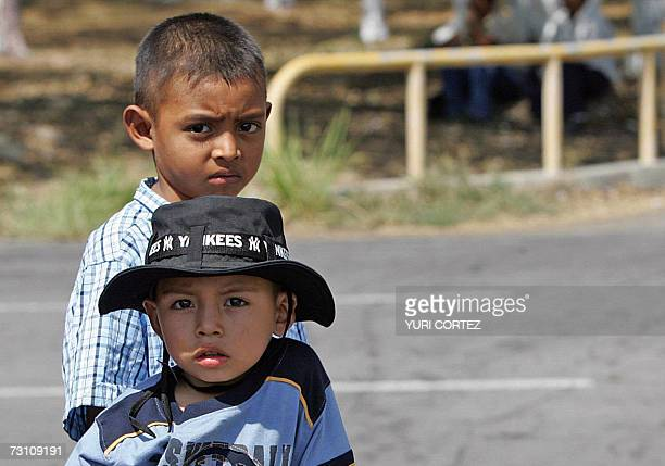 Two boys relatives of some members of a group of 117 people deported from the United States wait for their arrival at El Salvador's international...