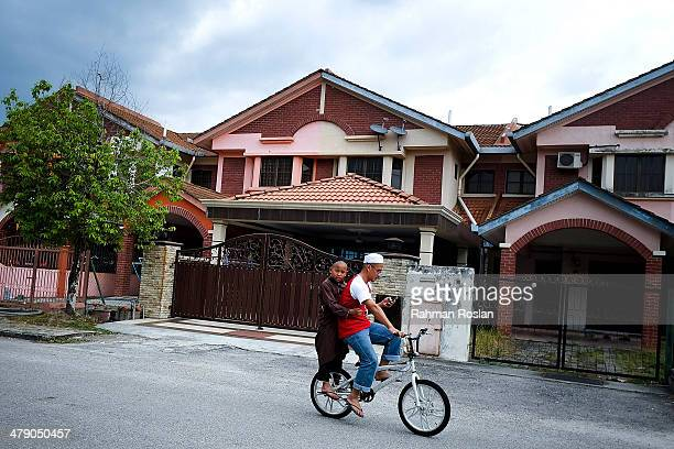 Two boys ride a bicycle past the house of Fariq Abdul Hamid the missing Malaysian airliner's copilot in Shah Alam on March 16 2014 in Kuala Lumpur...