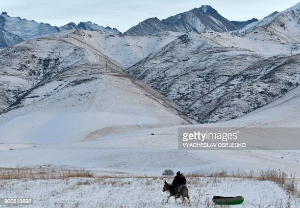 TOPSHOT Two boys ride a donkey towing an inflatable raft on a snowcovered path near the village of Kyzyl Birlik some 25km from Bishkek on January 3...