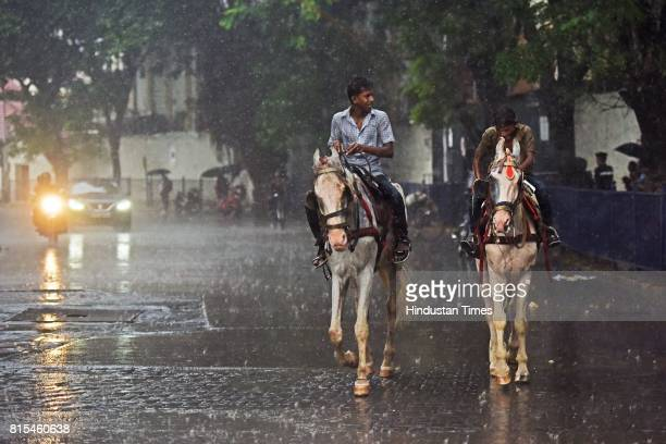 Two boys ride on a horse through the heavy rain near Colaba on July 15 2017 in Mumbai India The IMD issued warnings to the Maharashtra and Gujarat...