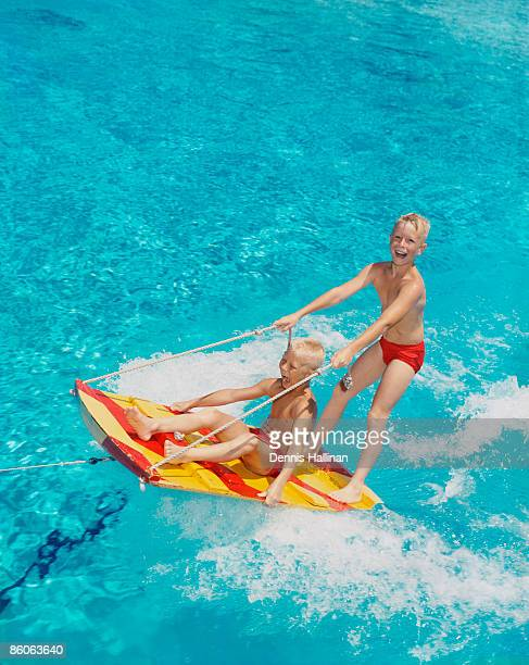 Two Boys Riding on a Water Sled