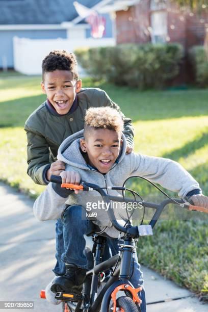 twee jongens rijden op een fiets - stadsdeel stockfoto's en -beelden
