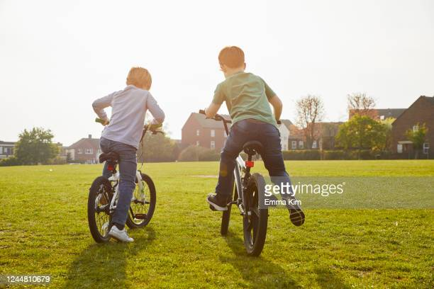 two boys riding their bmx bikes in a park. - boys stock pictures, royalty-free photos & images