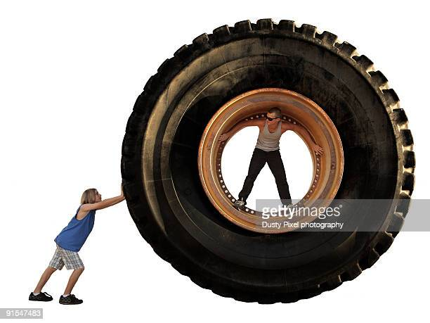 Two boys roll around a giant mining tire