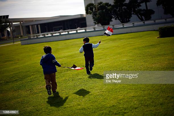 Two boys run with Egyptian flags at a protest against the regime of Egyptian President Hosni Mubarak February 5 2011 in the Westwood neighborhood of...