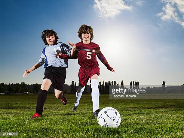 Two boys (10-11) running after football on pitch