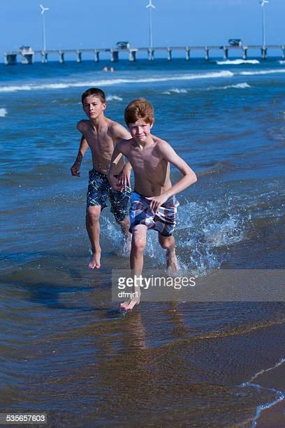 two boys running along beach - jungen in badehose 12 jahre stock-fotos und bilder