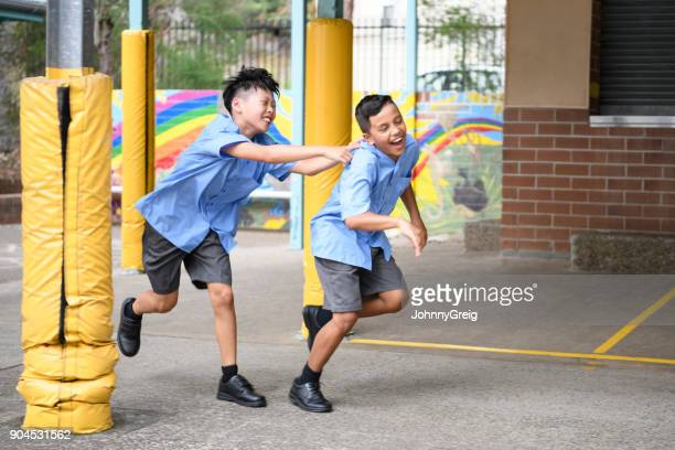 two boys running and laughing in school playground - sydney chase stock pictures, royalty-free photos & images