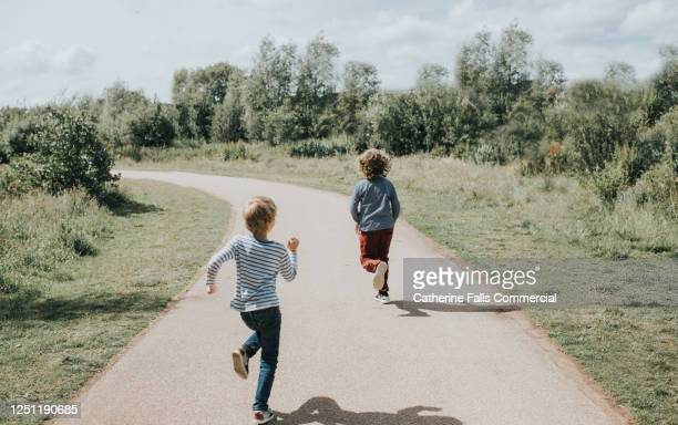 two boys running down a yellow path in bright sun - escaping stock pictures, royalty-free photos & images