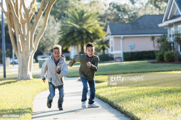 two boys running on sidewalk racing each other - side by side stock pictures, royalty-free photos & images