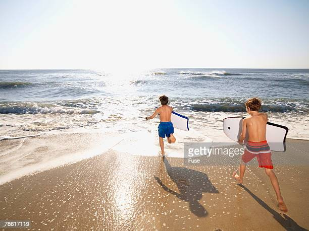 Two Boys Running with Bodyboards to the Ocean