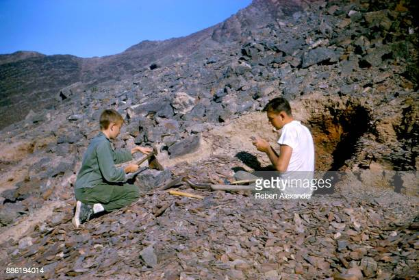 Two boys search for fossils in a shale outcroppping in the Mojave Desert in southern California near Amboy California The area's Marble Mountains...