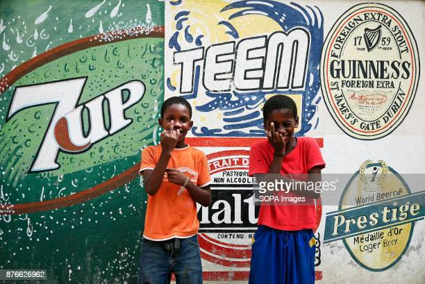 Two boys seen posing for a photo in front of a western advertising board On January 12th 2010 an earthquake hit this poor Caribbean country The...