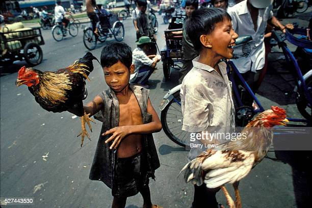 Two boys selling cockerels for cock fighting in a busy street in Saigon, Vietnam