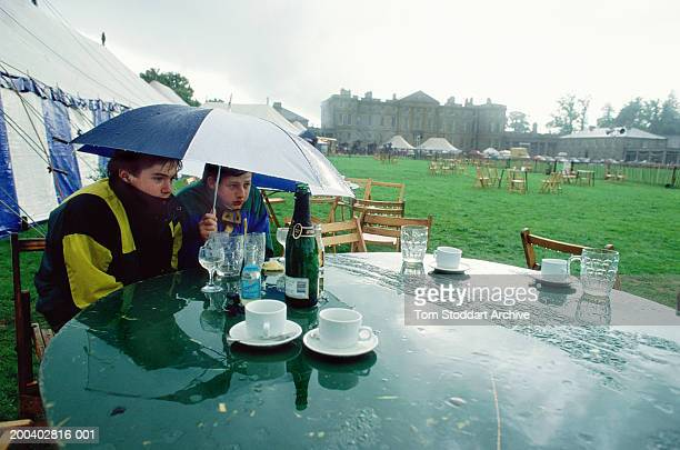 Two boys shelter under an umbrella during a rain downpour at the Rutland Show which washed out the planned country events and competitions UK April...