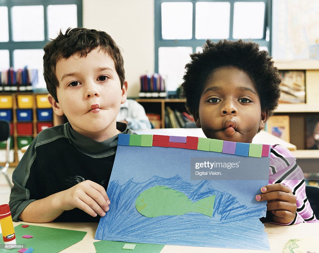 Two Boys Showing a Drawing in a Classroom and Pulling Funny Faces : Stock Photo