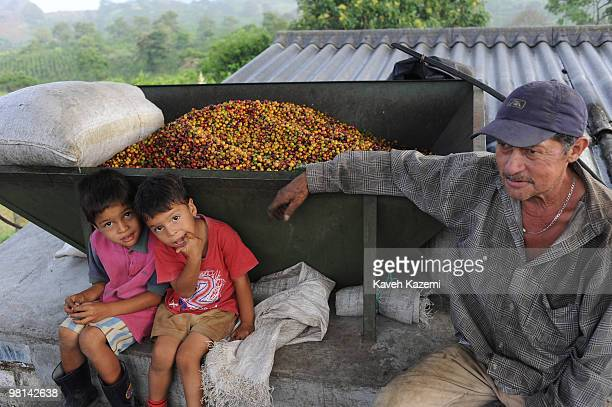 Two boys sit by a machine where coffee beans are loaded into for further process in a farms in Combia Risaralda Risaralda is a department of Colombia...