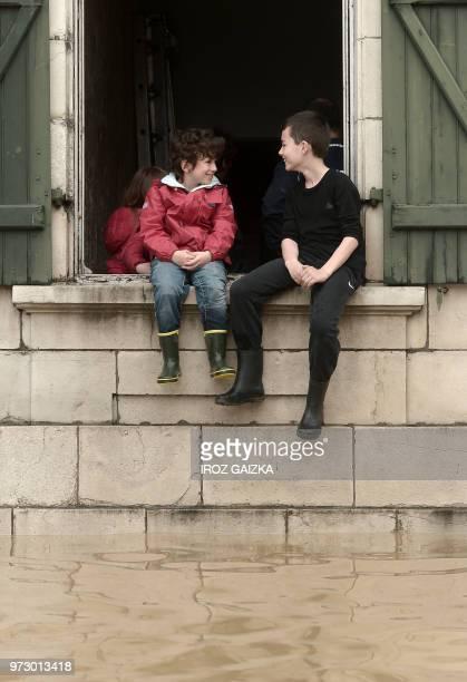 Two boys sit on the window sill as they watch flood waters flow underneath following heavy rains in SaliesdeBearn south western France on June 13 2018
