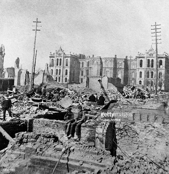Two boys sit on top of a partial stone wall in the wreckage of a burned-out building at Madison and Clark Streets, with the Court House in the...