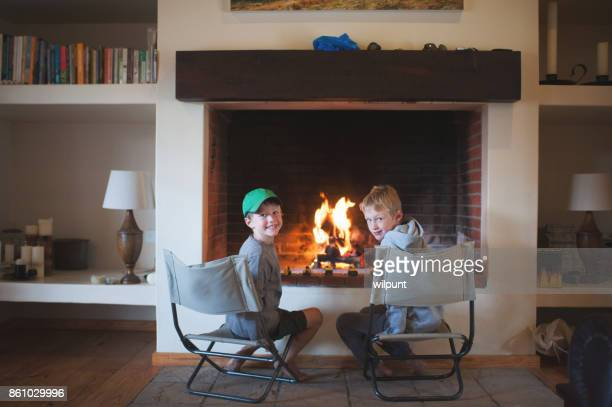 Two Boys sitting at indoor fire looking at camera