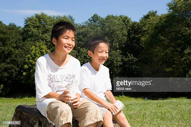 Two Boys Sitting at Park