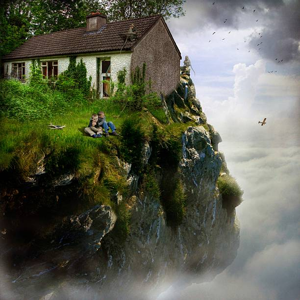 Two boys sitting at the edge of a cliff in front of an abandoned house, Republic of Ireland