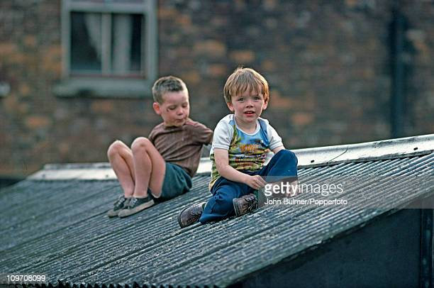 Two boys sitting on a shed roof in Manchester England in 1976